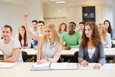 college woman raising hand in class to ask a question